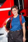 Lycklig brandmanHolding Helmet Against Firetruck Royaltyfri Bild