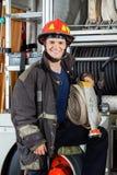 Lycklig brandmaninnehavslang, medan stå med lastbilen Royaltyfria Foton
