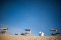 Lycklig brud, brudgumanseende på stranden och att kyssa och att le som skrattar i deras bröllopsresa Royaltyfri Fotografi