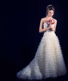 Lycklig brud för härlig försiktig kvinna i en vit bröllopsklänning med en drevkabin med en härlig bröllopfrisyr med vit flowe Royaltyfria Foton