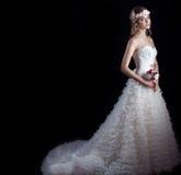 Lycklig brud för härlig försiktig kvinna i en vit bröllopsklänning med en drevkabin med en härlig bröllopfrisyr med vit flowe Royaltyfri Foto