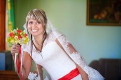 Lycklig brud med bröllopbuketten Arkivfoto