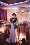 Lycklig brud med en stor bukett av rosor den h?rliga unga le bruden rymmer den stora gifta sig buketten med rosa rosor royaltyfri foto