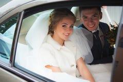 Lycklig brud och brudgum i bilen royaltyfria foton