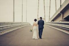 Lycklig brud och brudgum som firar bröllopdag Gift par som bort går på bron Långt familjelivvägbegrepp tonat arkivfoto