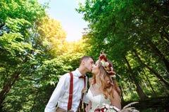 Lycklig brud och brudgum som går i sommarskogen Arkivfoto