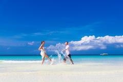 Lycklig brud och brudgum som har gyckel på en tropisk strand Royaltyfri Foto