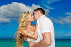 Lycklig brud och brudgum som kysser på en tropisk strand Blått hav i t Arkivbild