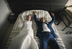 Lycklig brud och brudgum som ligger på säng på hotellrum Royaltyfria Bilder