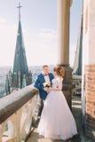 Lycklig brud och brudgum som poserar på balkongen av den gamla gotiska domkyrkan Royaltyfria Bilder