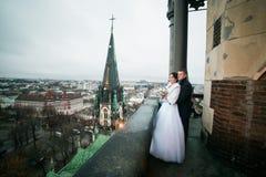 Lycklig brud och brudgum som rymmer sig på balkongen av den gamla gotiska domkyrkan Royaltyfria Bilder