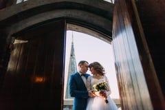 Lycklig brud och brudgum som rymmer sig på balkongen av den gamla gotiska domkyrkan Sikt från dörröppningen Arkivfoton