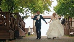Lycklig brud- och brudgumspring och att skratta på en träbro i parkera på bröllopet går lager videofilmer