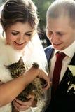 Lycklig brud och stilfull brudgum som rymmer den förtjusande söta lilla satsen Royaltyfri Fotografi