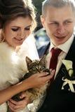 Lycklig brud och stilfull brudgum som rymmer den förtjusande söta lilla satsen Royaltyfria Foton