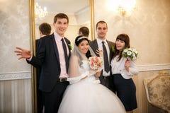 Lycklig brudgum, brud, groomsman, brudtärnaställning nära en spegel i rummet royaltyfri bild