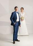 Lycklig brudgum i dräkten som poserar på studion med bruden Arkivfoto