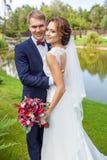Lycklig brudgum och brud som kramar, medan stå på grönt gräs nära royaltyfri fotografi