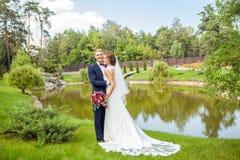 Lycklig brudgum och brud som kramar, medan stå på grönt gräs nära arkivbild