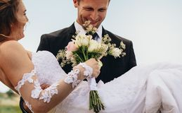 Lycklig brudgum som bär den härliga bruden arkivfoto