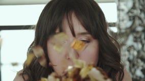 Lycklig brunett som ler och blåser guld- omslag på kamera lager videofilmer