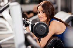 Lycklig brunett som utarbetar i en idrottshall Arkivfoto