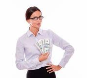 Lycklig brunettaffärskvinna som rymmer några pengar Royaltyfri Foto