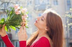 Lycklig brunettflicka i den röda skjortainnehavbuketten av färgrika blommor utanför under den tidiga våren fotografering för bildbyråer