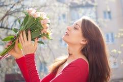 Lycklig brunettflicka i den röda skjortainnehavbuketten av färgrika blommor utanför under den tidiga våren royaltyfri fotografi