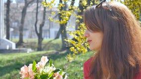 Lycklig brunettflicka med solglasögon på huvudet i den röda skjortainnehavbuketten av färgrika blommor utanför under tidigt stock video