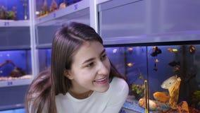 Lycklig brunettflicka som ser den tropiska fisken arkivfilmer