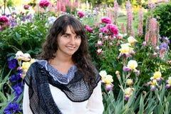Lycklig brunettkvinna i blommamiljö Royaltyfri Fotografi