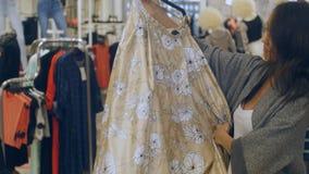 Lycklig brunettkvinna med klänningen på hängare i galleria Arkivfoton