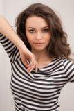 Lycklig brunettkvinna med lockigt hår och perfekt posera för leende arkivbilder