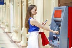 Lycklig brunettkvinna som återtar pengar från kreditkort på ATM Royaltyfri Foto