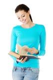 Lycklig brunettkvinna som läser den intressanta boken Royaltyfri Foto