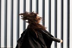 Lycklig brunettmodell med hår som blåser i vinden som går på th Arkivfoton