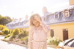 Lycklig brunettmodell som poserar på staden i strålar av solen Fotografering för Bildbyråer