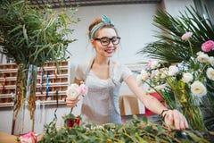 Lycklig bukett för kvinnablomsterhandlaredanande i blomsterhandel Arkivfoto