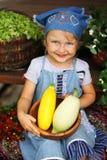 Lycklig bunke för liten flickaholdingа med grönsaker Arkivbild