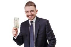 Lycklig bussinessman som rymmer 20 amerikanska dollarräkningar i hans hand som isoleras på vit bakgrund arkivbild