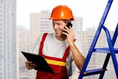 Lycklig byggmästare som talar på telefonen arkivbilder