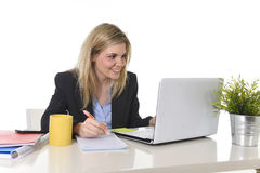 Lycklig Caucasian blond affärskvinna som arbetar på bärbar datordatoren på det moderna kontorsskrivbordet Arkivbilder