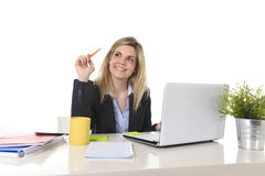 Lycklig Caucasian blond affärskvinna som arbetar på bärbar datordatoren på det moderna kontorsskrivbordet Royaltyfri Foto