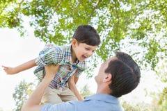 Lycklig Caucasian fader och son som spelar i parkera Arkivbild