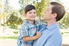 Lycklig Caucasian fader och son som tillsammans talar i parkera Fotografering för Bildbyråer