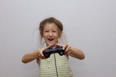 Lycklig Caucasian flicka som spelar videospel som rymmer den modiga kontrollanten Arkivfoton