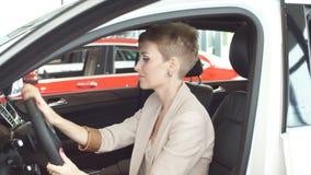 Lycklig caucasian kvinna som omfamnar hennes nya bil på den auto återförsäljaren arkivfilmer