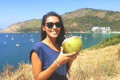 Lycklig Caucasian kvinna som rymmer den thailändska unga kokosnötcoctailen med att förbluffa den Phuket sikten thailand Arkivfoton