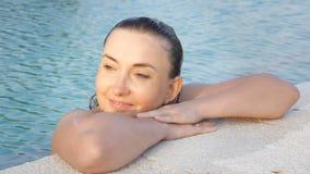 Lycklig caucasian kvinna som tycker om vatten på kanten av pölen stock video
